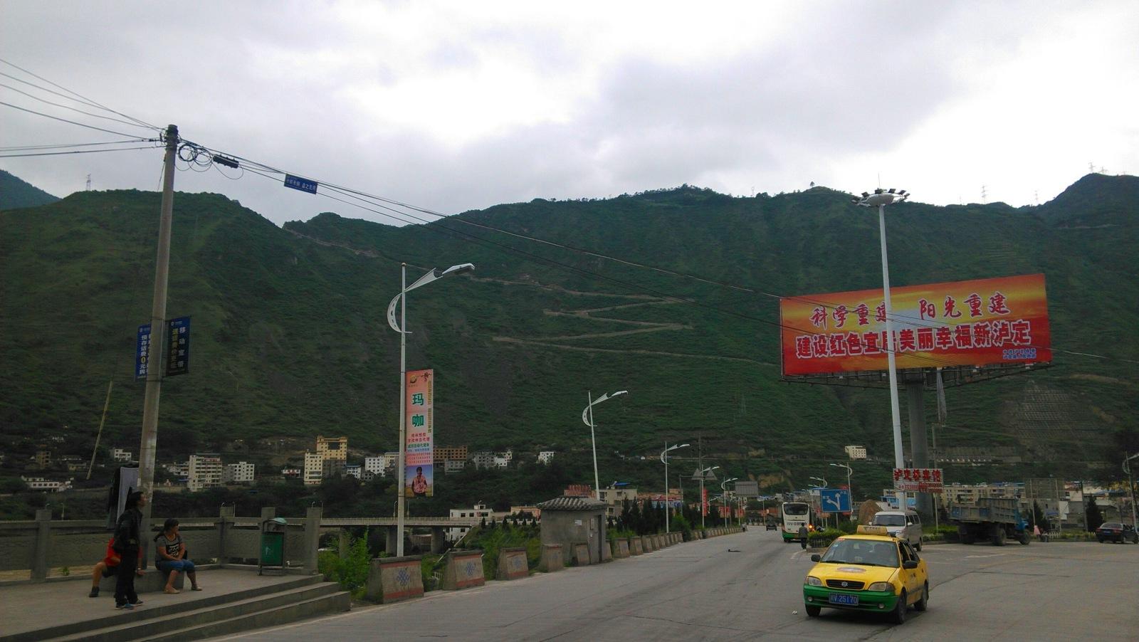 """泸定城区路口,对面山上的那条""""折多路""""还是挺炫酷的:p"""